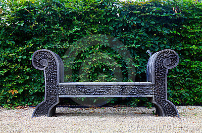 Antique wooden bench on pebble yard garden