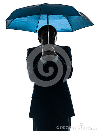 Anxious business man under umbrella silhouette