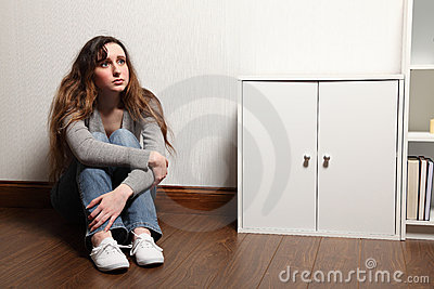 Anxious teenage girl sits alone on floor at home