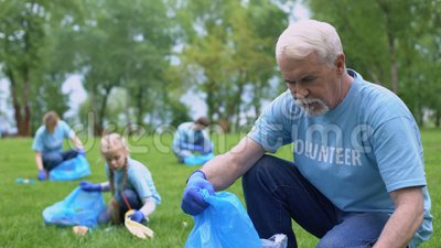 Anziani volontari raccolgono rifiuti di plastica e inseriscono spazzatura, evento ecologico video d archivio