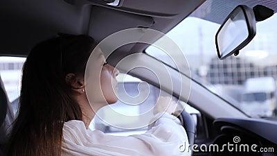 Aplique rímel com pincel Condução ilegal Linda jovem olha no espelho retrovisor para aplicar maquiagem vídeos de arquivo