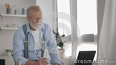 Aposentado idoso moderno, com óculos para visão, trabalha duro com suco de bebidas em laptop e grava dados para vídeos de arquivo