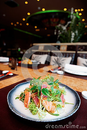 Appetizer with rare fried tuna and salmon on table