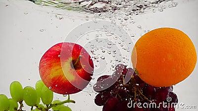 Apple, πορτοκάλι και σταφύλια που περιέρχονται στο νερό με τις φυσαλίδες σε σε αργή κίνηση Καρπός στην άσπρη ανασκόπηση απόθεμα βίντεο