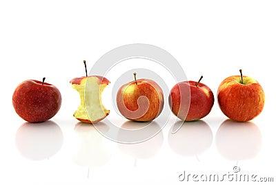 Apple core among whole apples