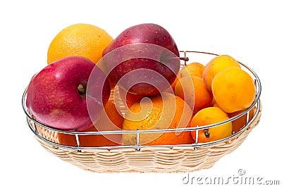 Apple, orange, apricot on bowl isolated on white