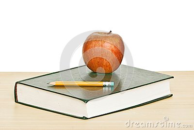 Apple and pencil on top of book