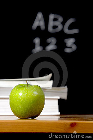 Apple and stack of books in classroom