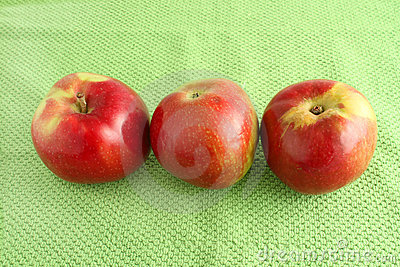 Apple trio on green cloth background