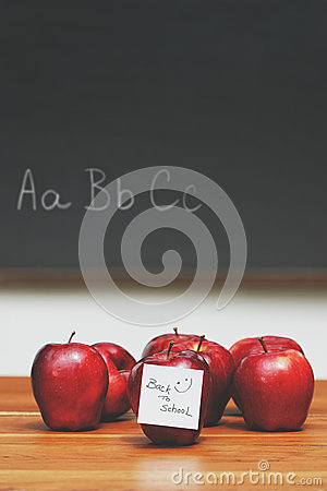 Apples with note on desk with blackboard in background