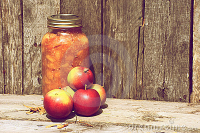 Apples and preserves on wood.