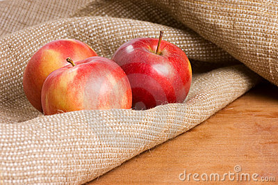 Apples on a sacking on a wooden table