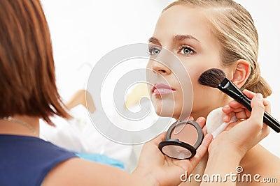 Applying blush on cheeks with blush brush