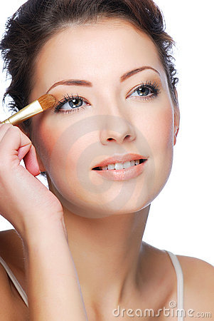 Applying eyeshadow using eyeshadow brush