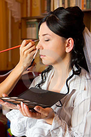 Applying makeup to the bride