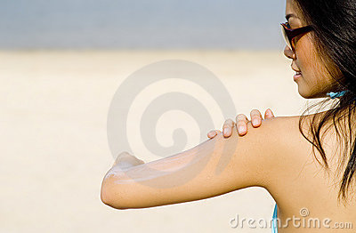 Applying Suncream At Beach