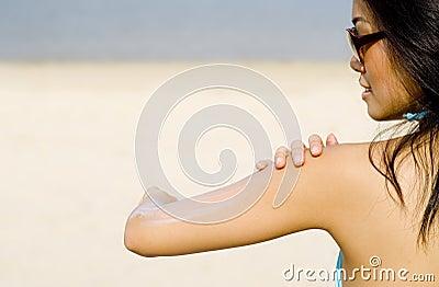 Applying Suncream At Beach
