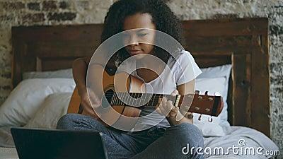 Aprendizagem concentraing da menina afro-americano atrativa do adolescente jogar a guitarra usando o laptop que senta-se na cama  filme