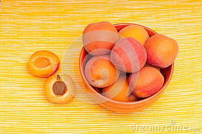 Apricots with kernel on a yellow tablecloth
