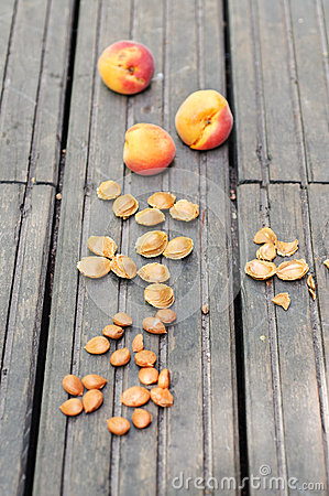 Apricots and pits on a wooden table