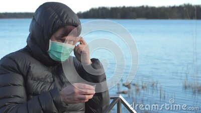 A lady trying to put on her face mask in Finland stock footage