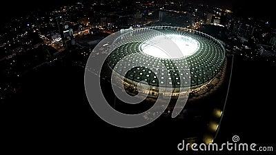 Arène de sports énorme brillant avec des lumières au coeur de la mégalopole de nuit, tir aérien clips vidéos