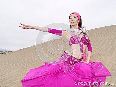 Arab dancer at dunes with sword