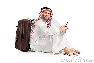 Arab man sitting near a suitcase