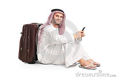 Arab man sitting near a suitcase