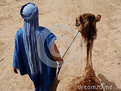 Arab man walking camel