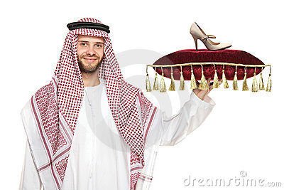 An arab person holding a pillow with a shoe on it