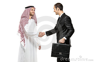 An Arab person shaking hands with a businessman