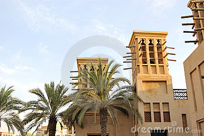 Arabic building with wind towers during sunset