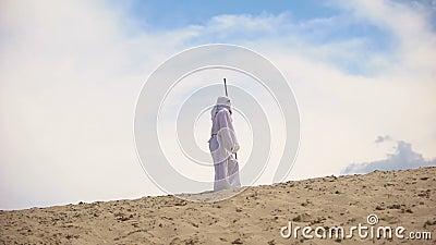 Arabisch met personeel dat in de woestijn loopt, naar doel gaat ondanks hitte en uitputting stock video
