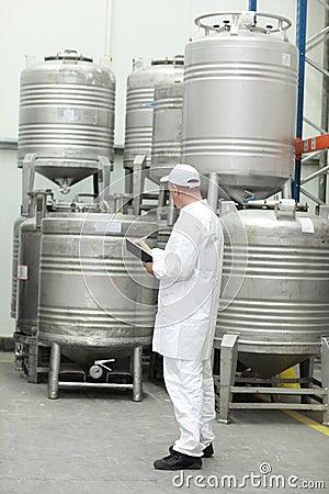 Arbeider die voorraden in levensmiddelenpakhuis controleert