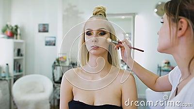 Arbeiten Sie den Stilisten um und ein Bild für das Topmodell schaffen Sie wurde für eine Fotoaufnahme oder eine Modeschau auf der stock video footage