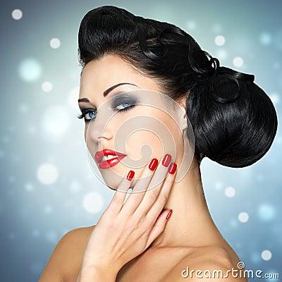 Arbeiten Sie Frau mit den roten Lippen, den Nägeln und kreativer Frisur um
