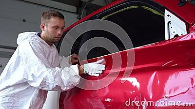 Arbeiter streicheln Farbe auf Karosserie von Hand in Handschuh in der Kfz-Dienstleistung stock footage