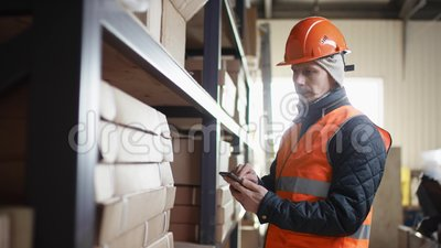 Arbeitnehmer mit Bart und Schnurrbart in einem Helm und Übergängen steht neben Racks und Schriftsatz auf seinem Handy stock footage