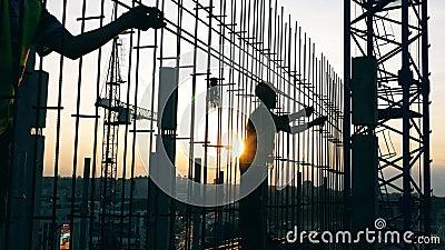Arbetare flyttar metallpoler när de bygger ett hus på en plats arkivfilmer