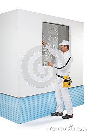 Arbetare som tejpar en ram av fönstret