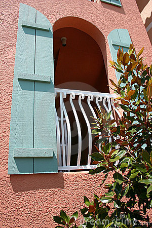 Arched window with blue shutters