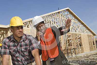 Architect On Call Gesturing Towards Site With Co-Worker
