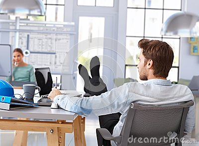 Architect designing with computer feet up on desk