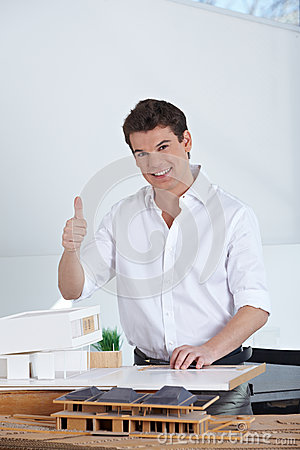 Architect with house model holding