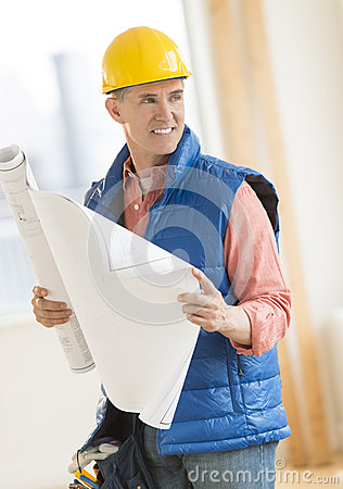Architect Looking Away While Holding Blueprint At Construction S
