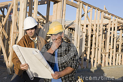 Architect Reviewing Blueprint With Worker