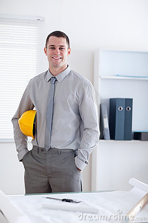 Architect standing and carrying a helm