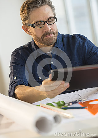 Architect Using Tablet Computer At Desk