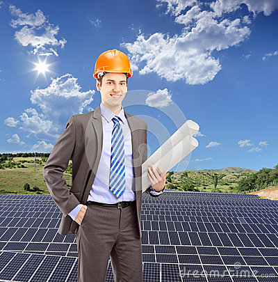 Architect wearing helmet and holding blueprints, with solar phot